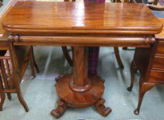 A Victorian mahogany fold over tea table on a pedestal base with four scroll feet, 74cm high x