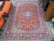 A large red ground Keshan rug with traditional design of blue central medallion, matching