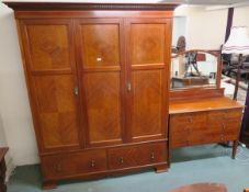 An inlaid mahogany three door fitted wardrobe with two lower drawers on bracket feet, 204cm high x