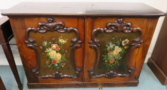 A two door cabinet with floral painted panels within carved frames, 86cm high x 129cm wide x 45cm