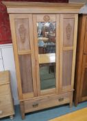 A wardrobe with carved panels and a single mirrored door over single drawer, 196cm high x 118cm wide