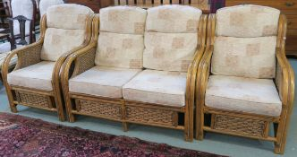 A cane three piece suite with two seater sofa and two chairs with a light fabric upholstery (3)