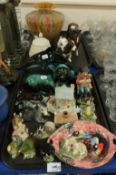 A lot comprising Poole pottery models of a dolphin and dog, a mottled multi coloured glass vase,