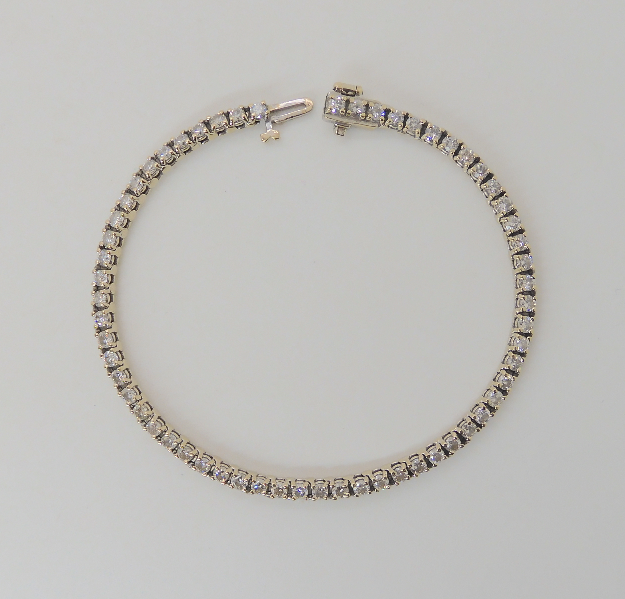 AN 18K WHITE GOLD DIAMOND LINE BRACELET set with estimated approx 2.7cts of brilliant cut
