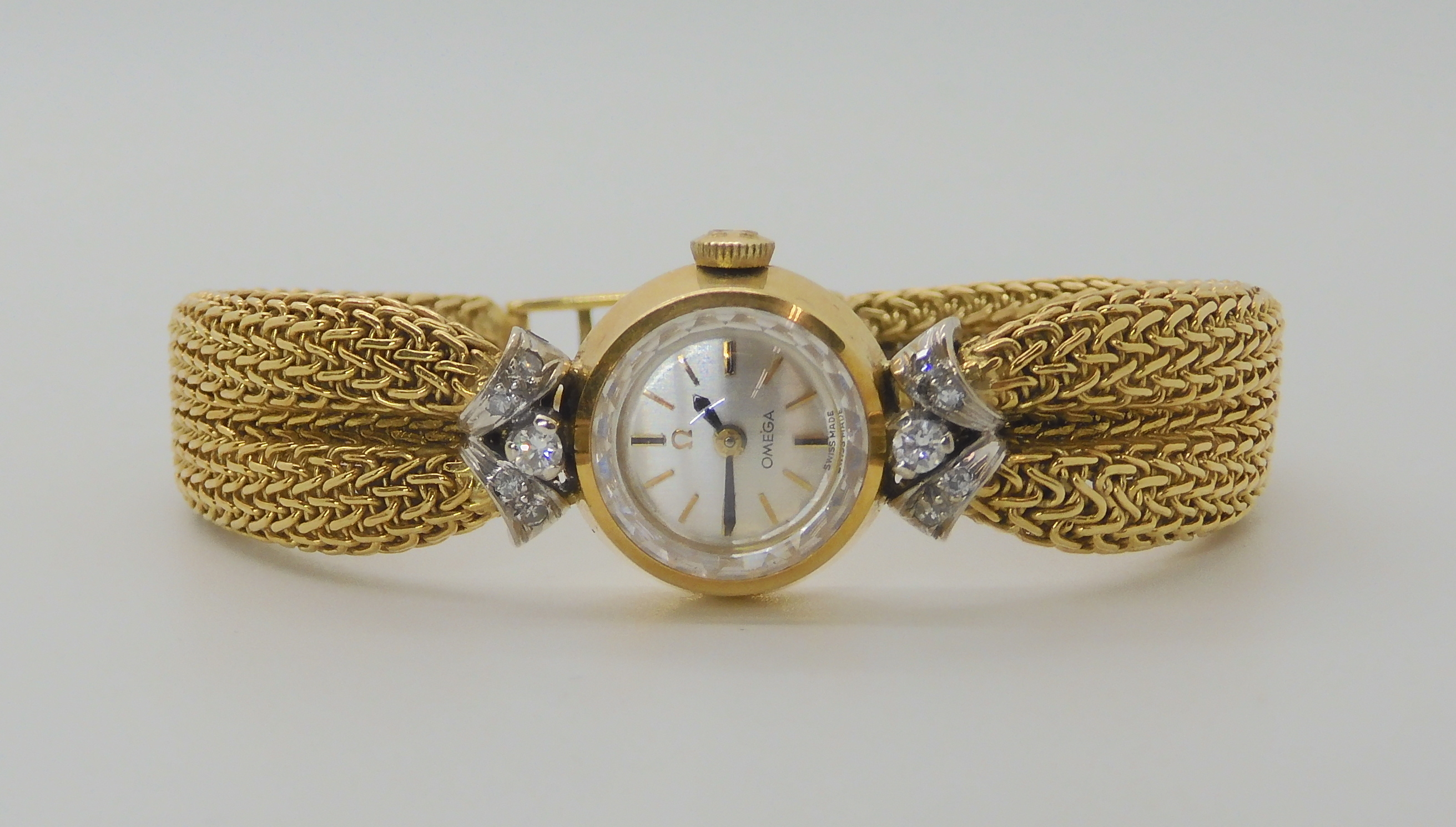 A LADIES 18CT GOLD OMEGA WITH DIAMONDS AND DECORATIVE STRAP the woven mesh strap in puckered to look