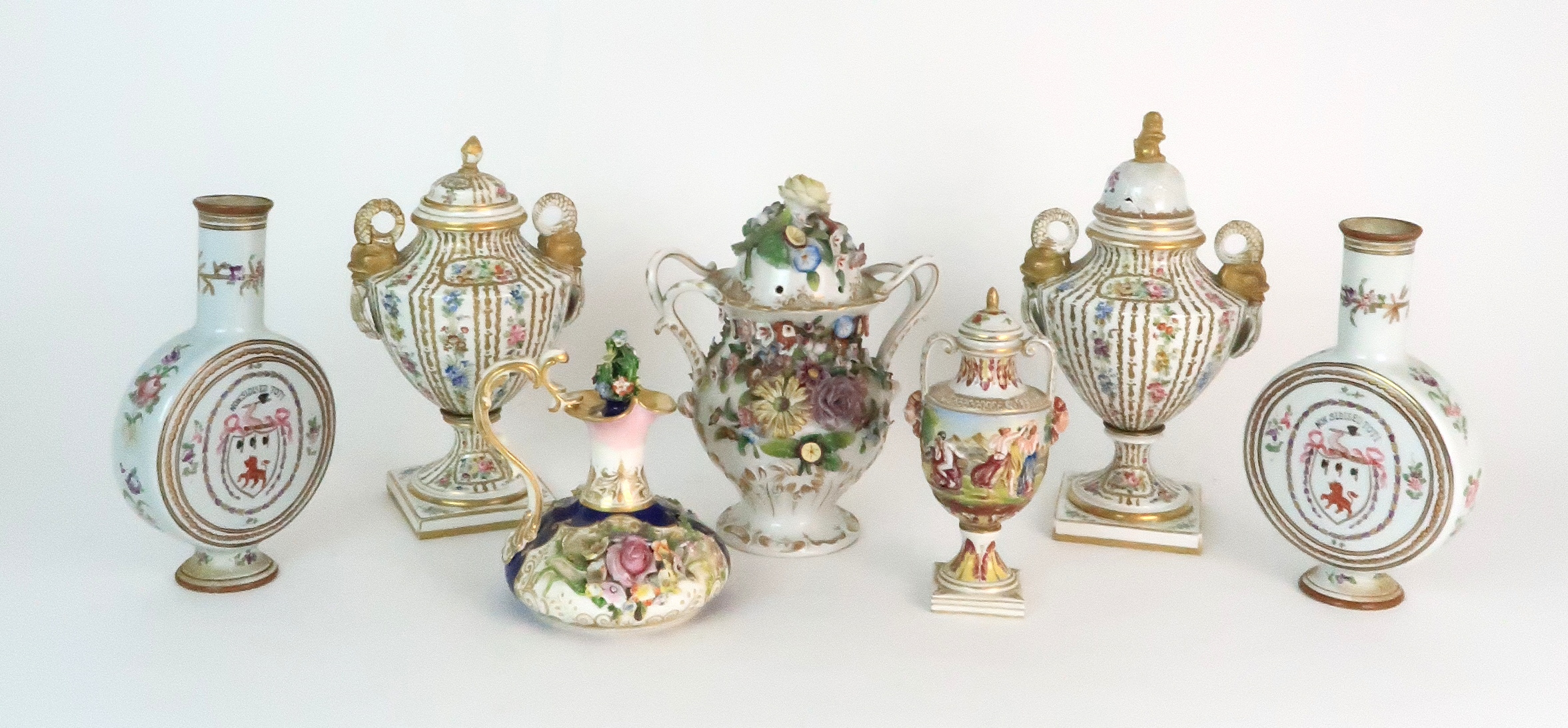A PAIR OF CONTINENTAL PORCELAIN URNS each decorated with strings of flowers and gilt dot and dash