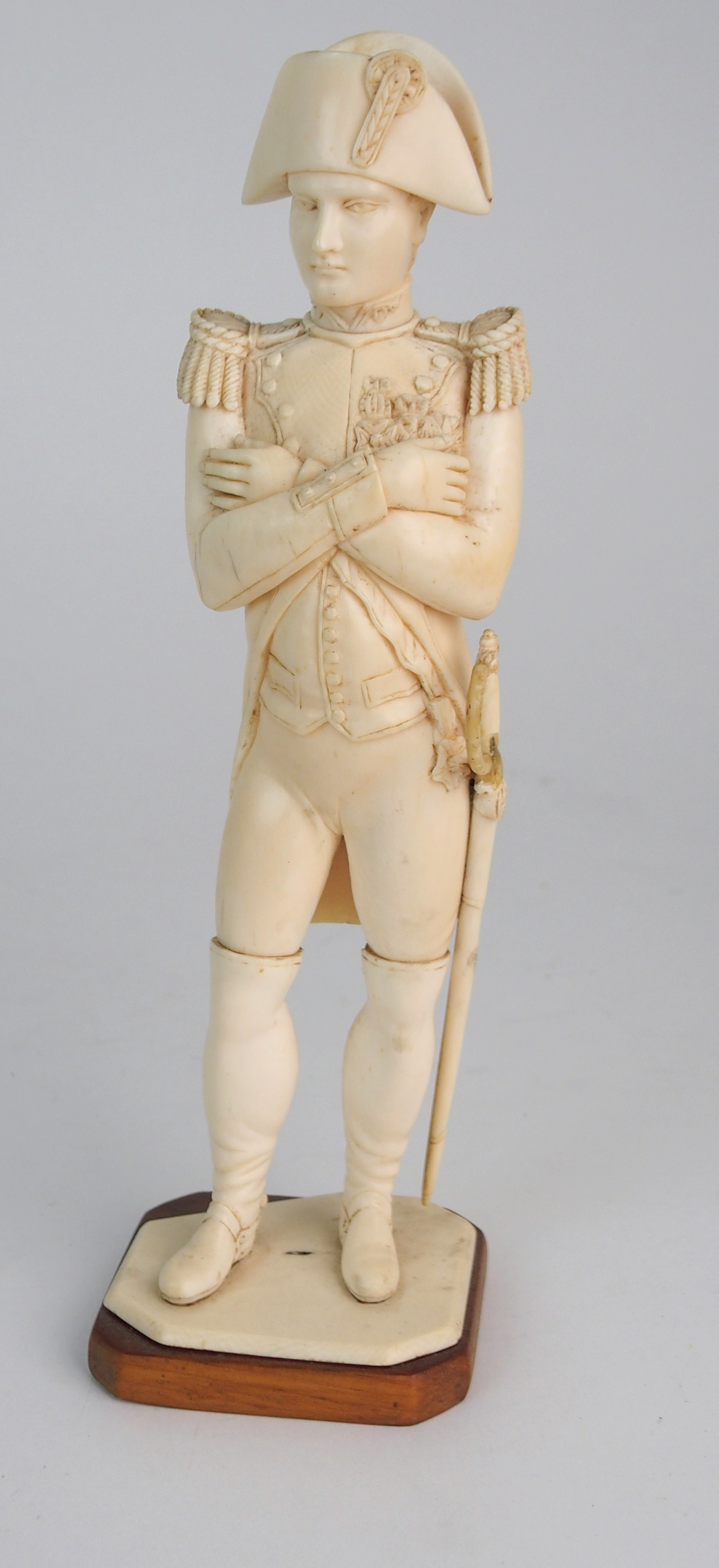 A LATE 19TH/EARLY 20TH CENTURY CARVED IVORY MODEL OF NAPOLEON in uniform with crossed arms, on