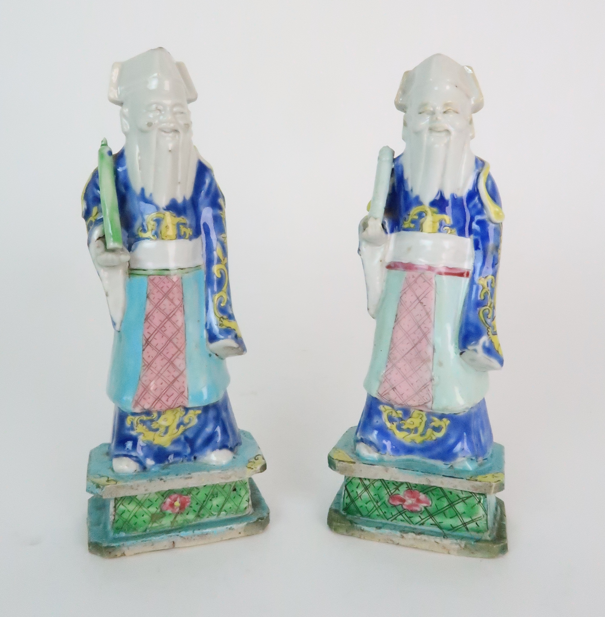 A PAIR OF CHINESE EXPORT MODELS OF OFFICIALS each standing and holding a scroll, diaper aprons and