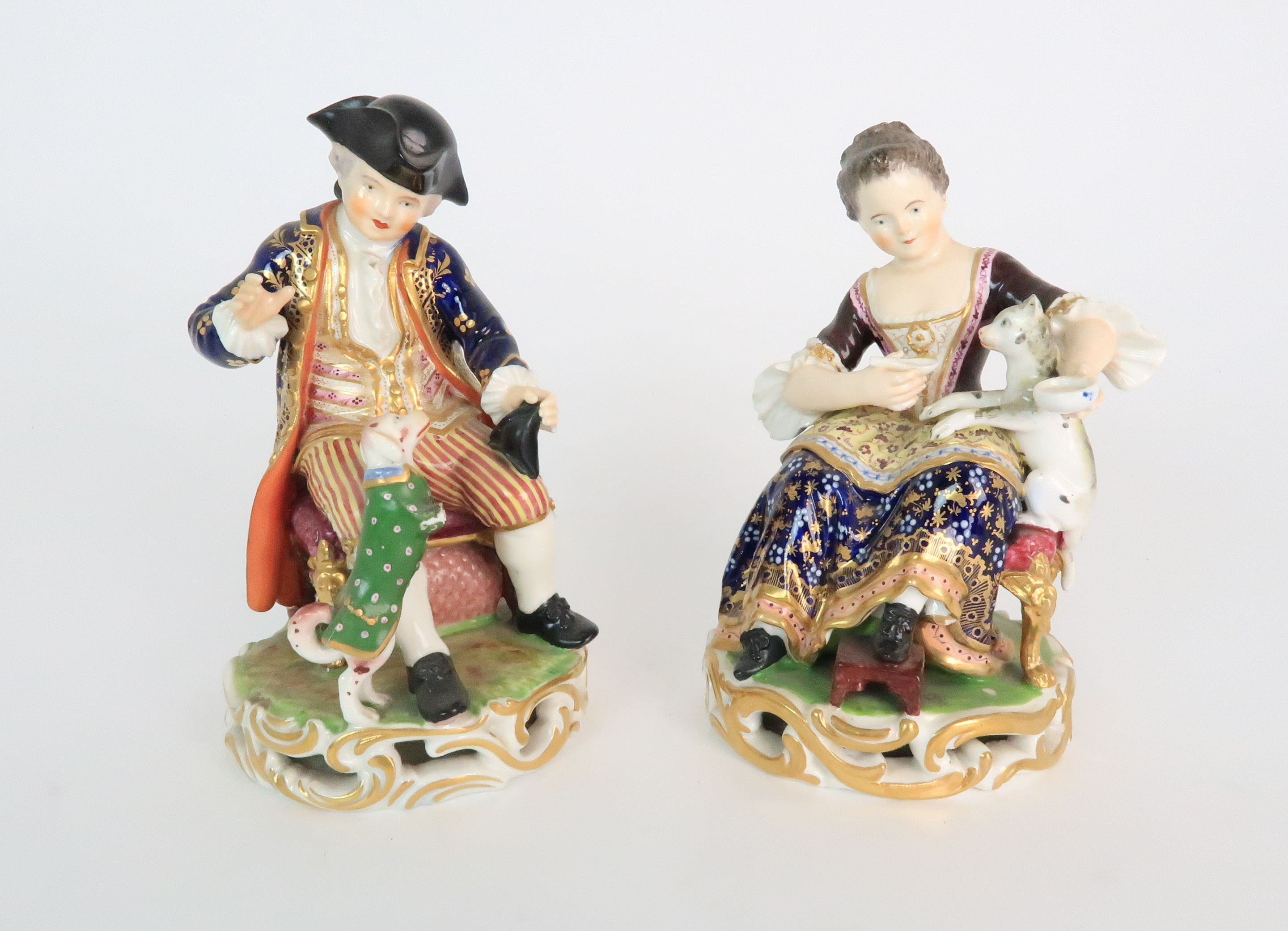 A PAIR OF DERBY PORCELAIN FIGURES early 19th century, modelled as a seated boy playing with a dog