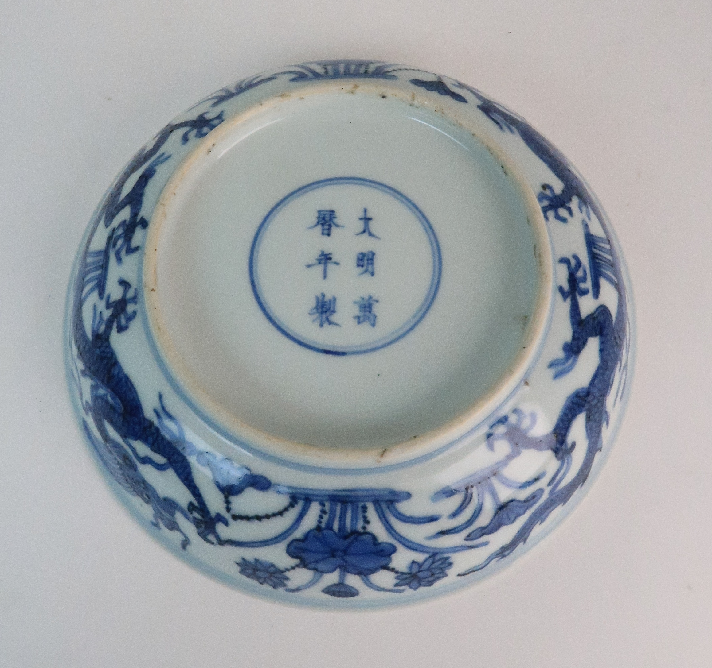 A CHINESE BLUE AND WHITE DISH painted with dragons amongst aquatic foliage, within a scrolling - Image 5 of 6