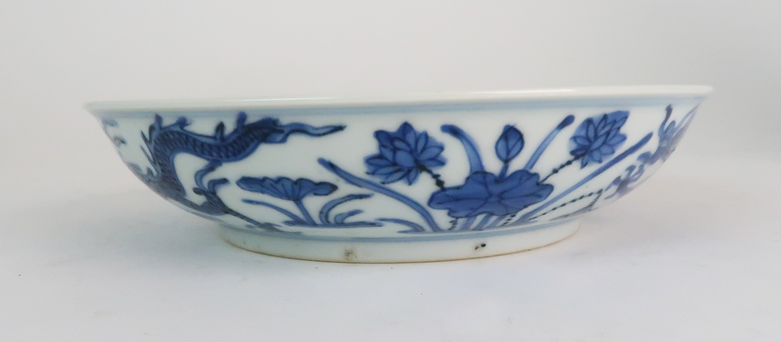 A CHINESE BLUE AND WHITE DISH painted with dragons amongst aquatic foliage, within a scrolling - Image 2 of 6