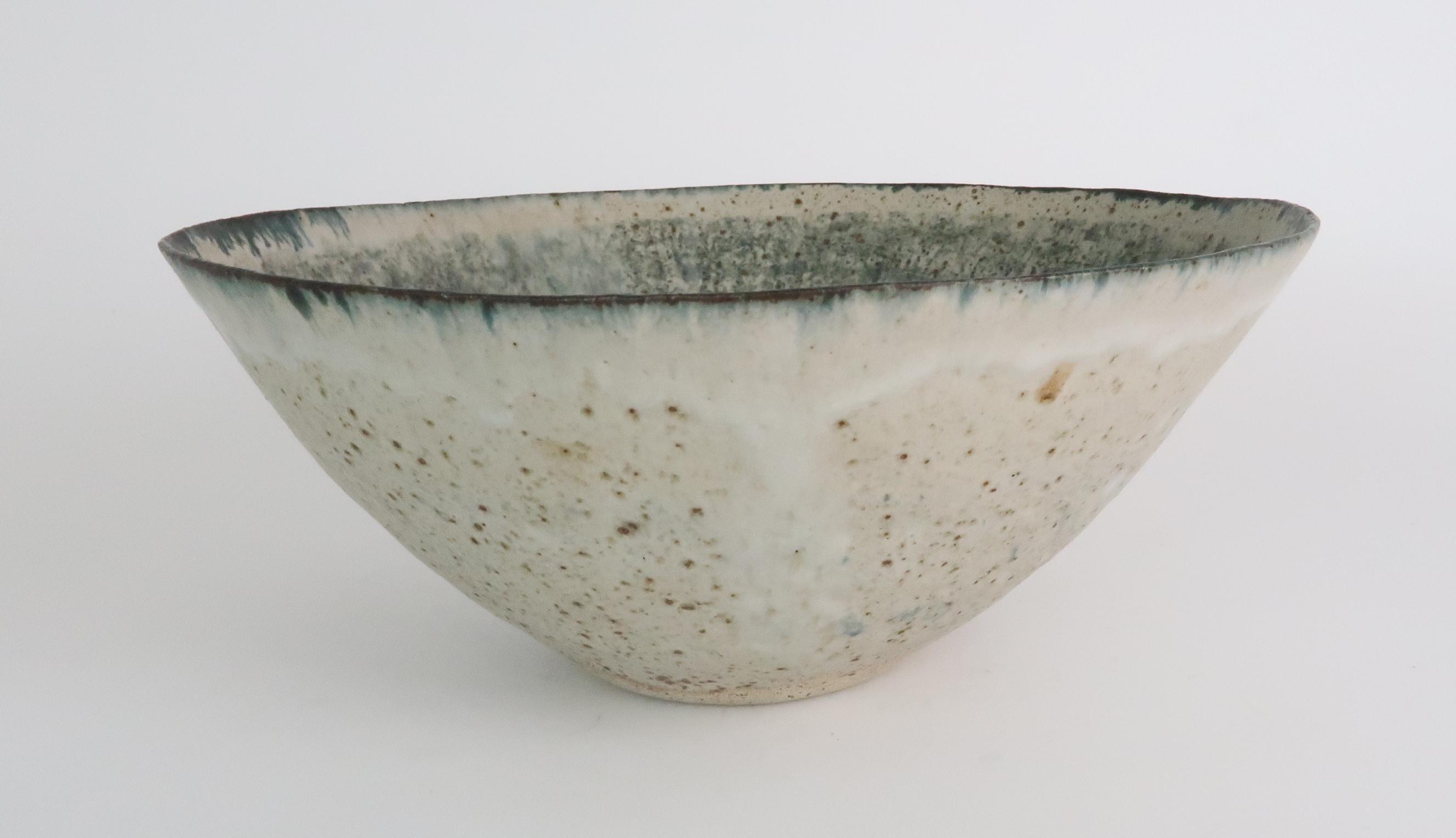 •BETTY BLANDINO (1927-2011) A stoneware bowl with slipware glaze, impressed mark to base, 32cm