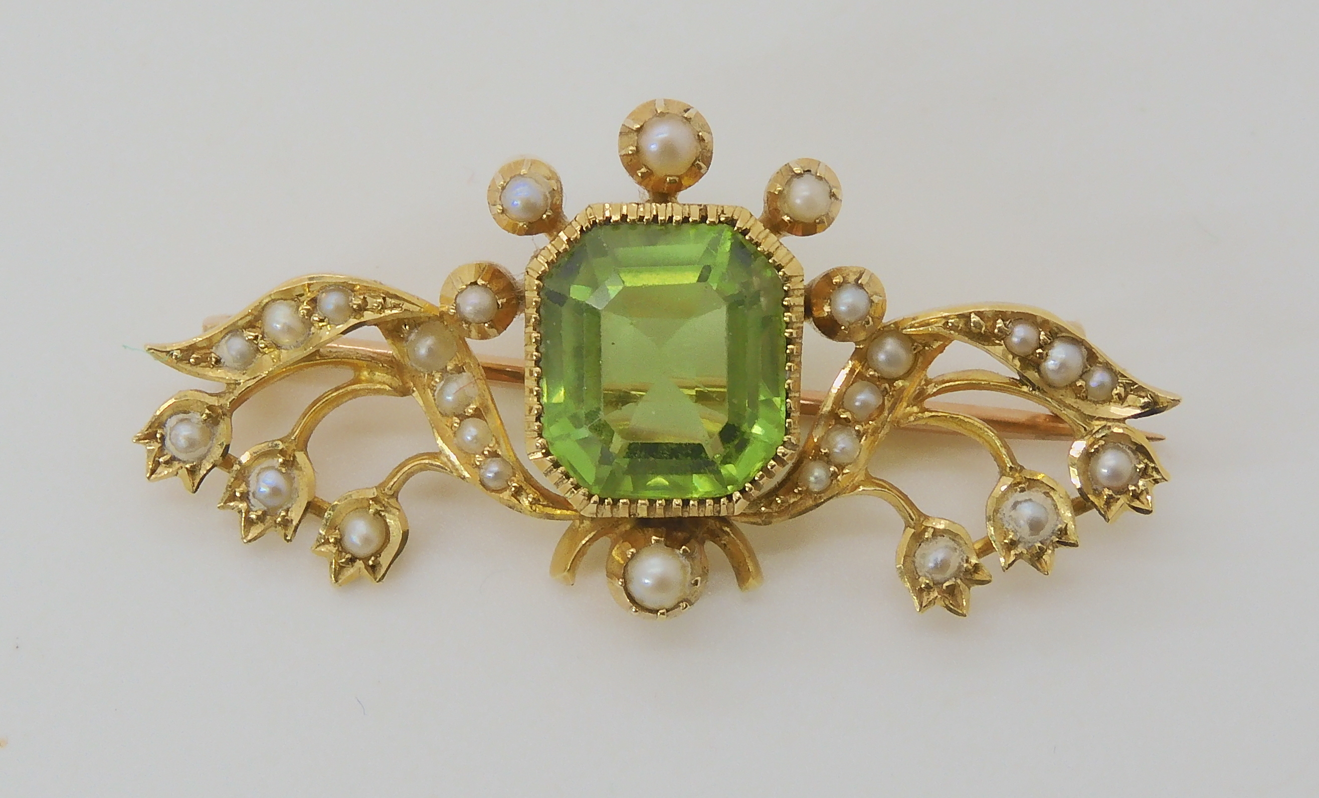 A 15CT GOLD PERIDOT AND PEARL EDWARDIAN BROOCH depicting lily of the valley, the peridot is