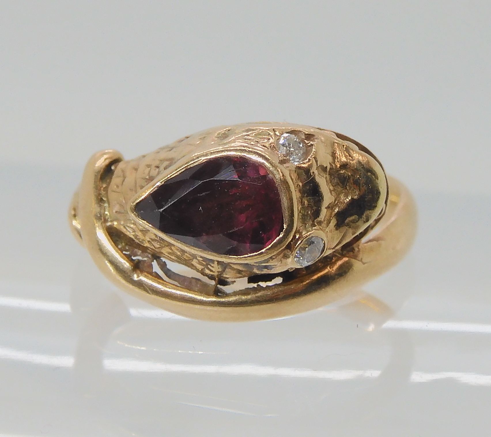 A 9CT ROSE GOLD GARNET AND DIAMOND SNAKE RING finger size J, weight 4.5gms Condition Report: Has