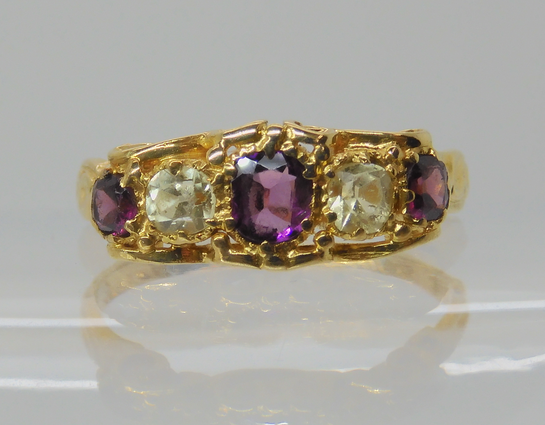 A VICTORIAN GEM SET RING inscribed and dated 1861, set with garnets and pale green gems, finger size
