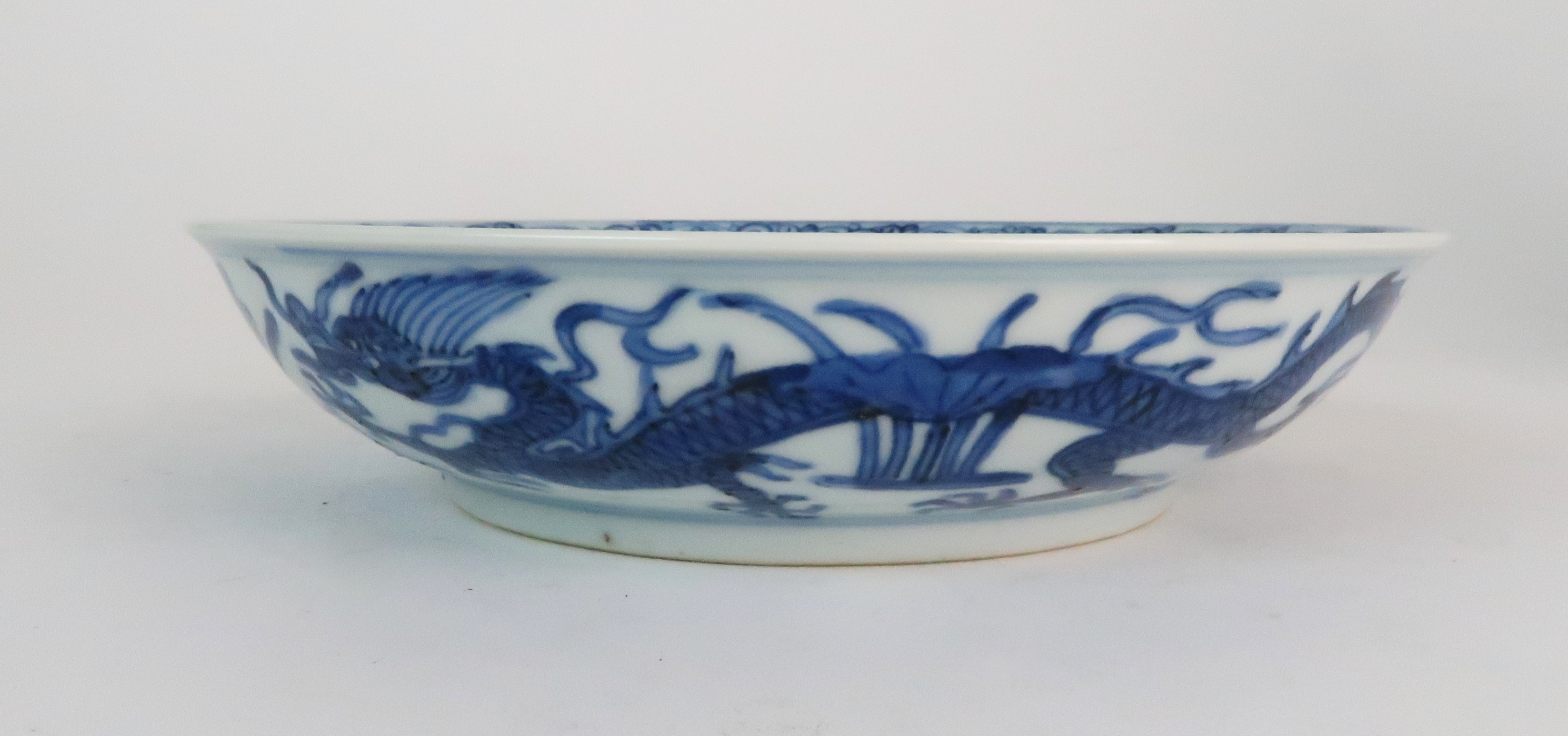 A CHINESE BLUE AND WHITE DISH painted with dragons amongst aquatic foliage, within a scrolling - Image 3 of 6