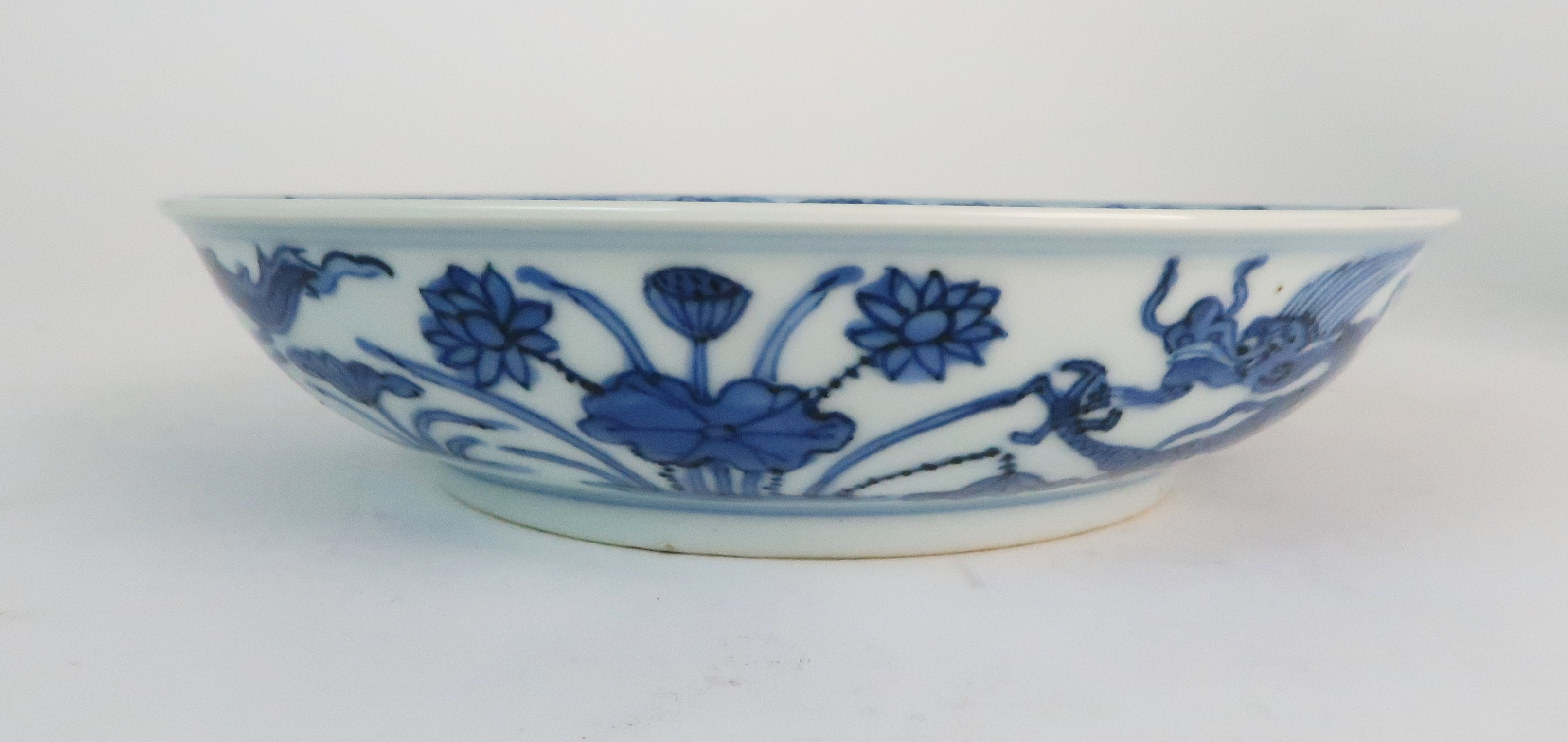 A CHINESE BLUE AND WHITE DISH painted with dragons amongst aquatic foliage, within a scrolling - Image 4 of 6