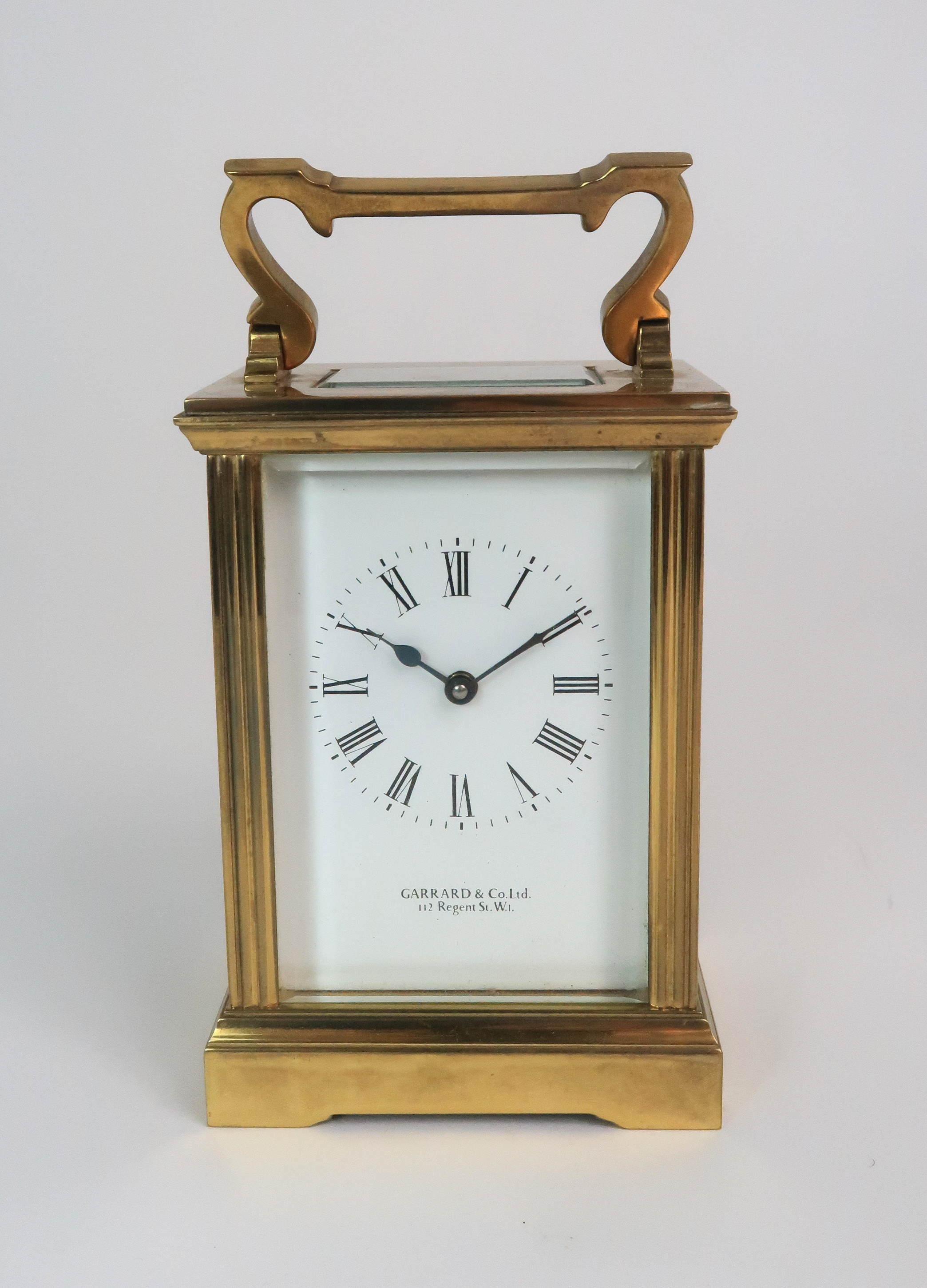A GARRARD AND CO BRASS AND GLASS CARRIAGE CLOCK the white dial with Roman numerals and the