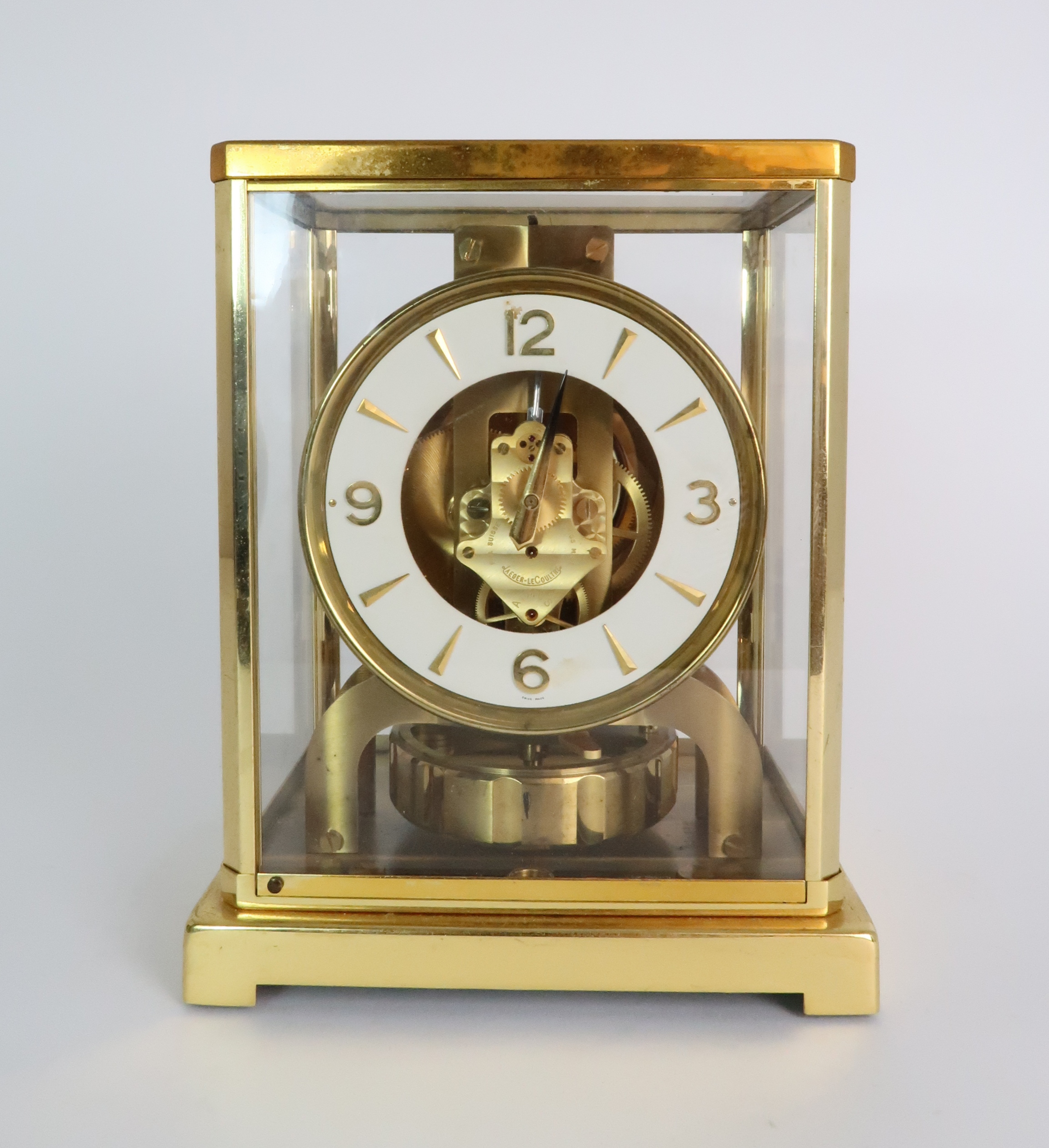A JAEGER LE COULTRE ATMOS CLOCK in glazed brass case, the white enamel chapter ring with applied