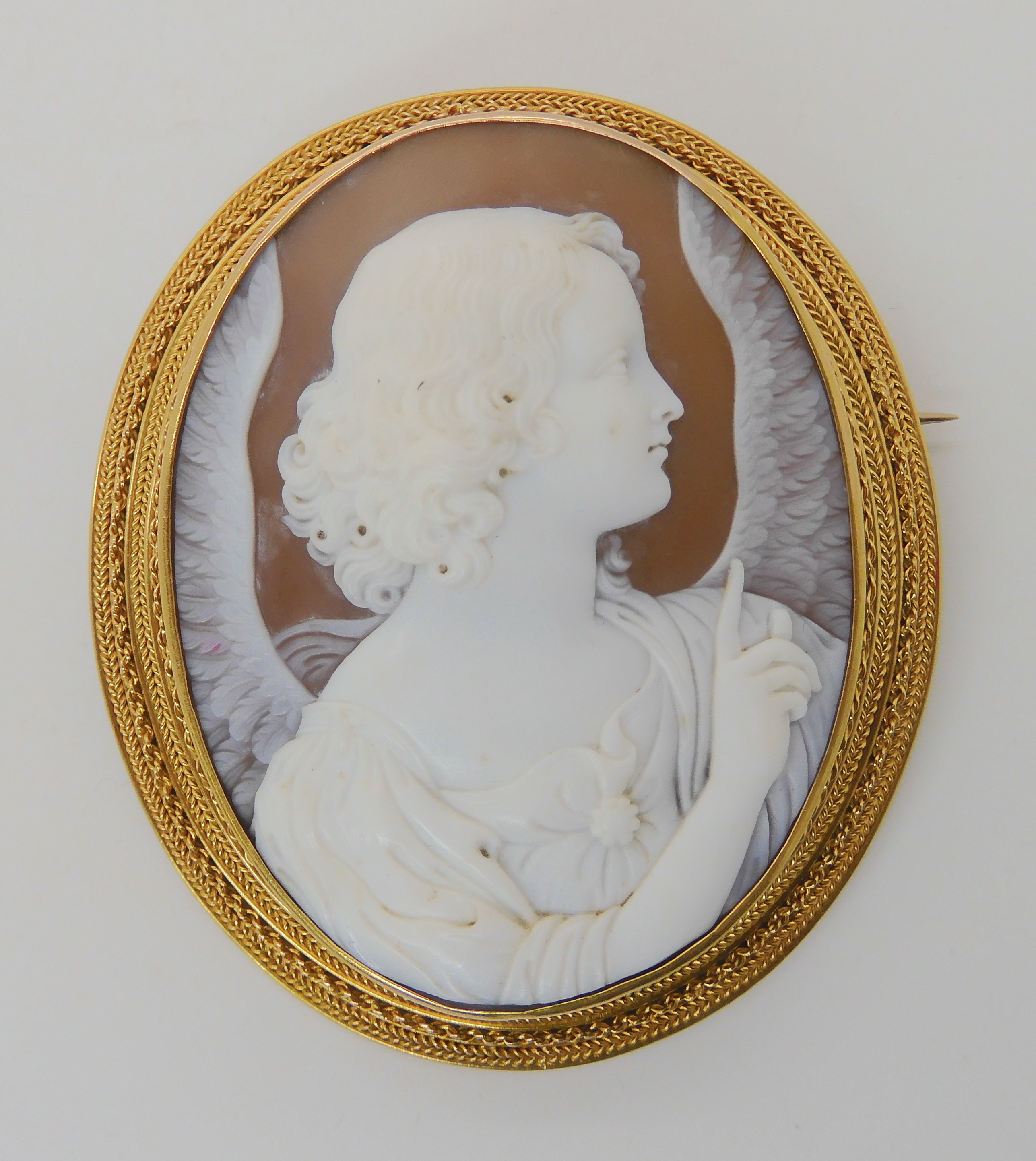 A LARGE FINE SHELL CAMEO OF AN ANGEL in a bright yellow metal rope wirework mount. Dimensions 6.