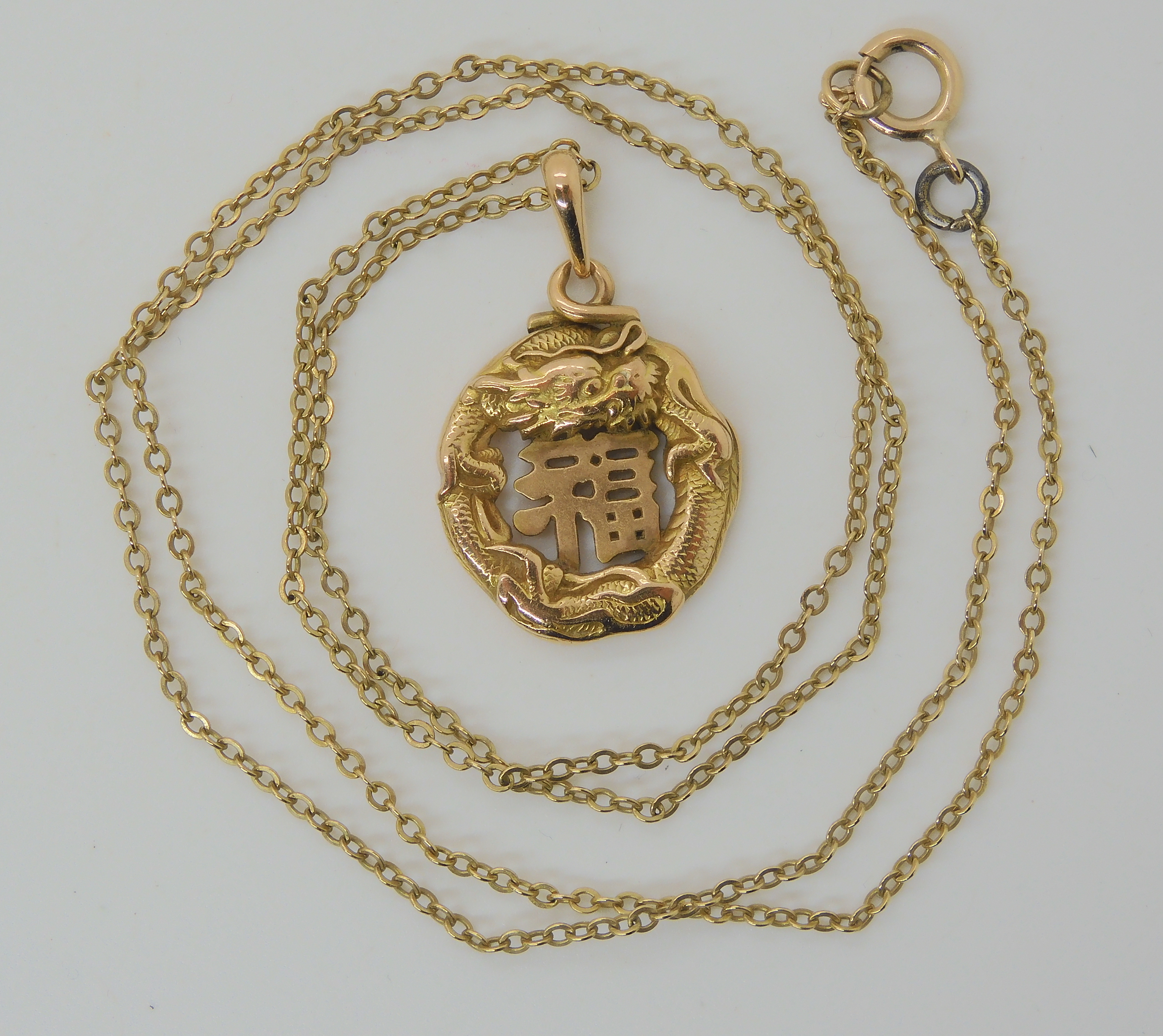 A CHINESE 16K GOLD DRAGON PENDANT the dragon coiled around a Chinese symbol, Chinese stamps to the