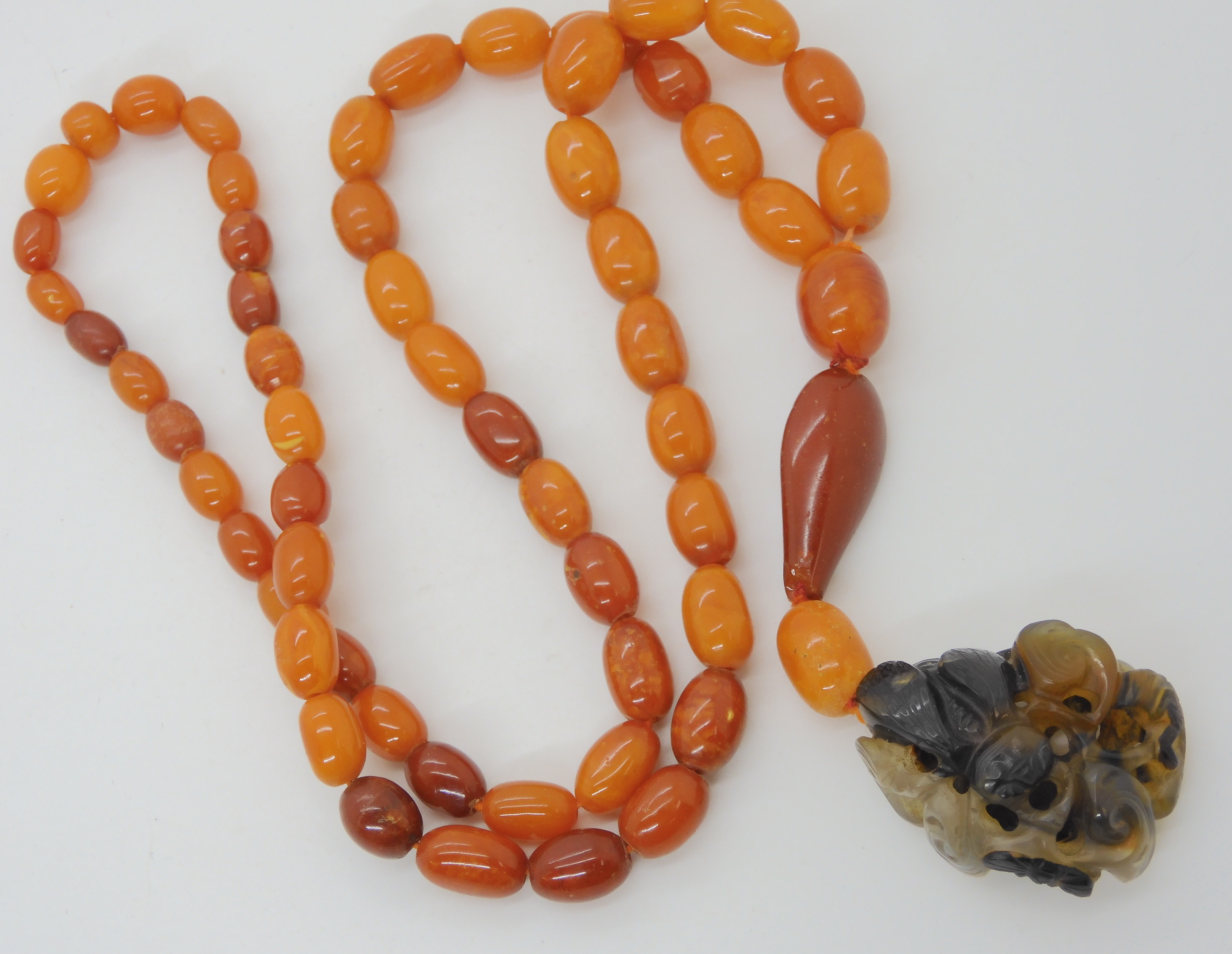 A STRING OF AMBER BEADS WITH A CHINESE CARVED PENDANT the agate pendant is carved with a bat, bee - Image 2 of 13