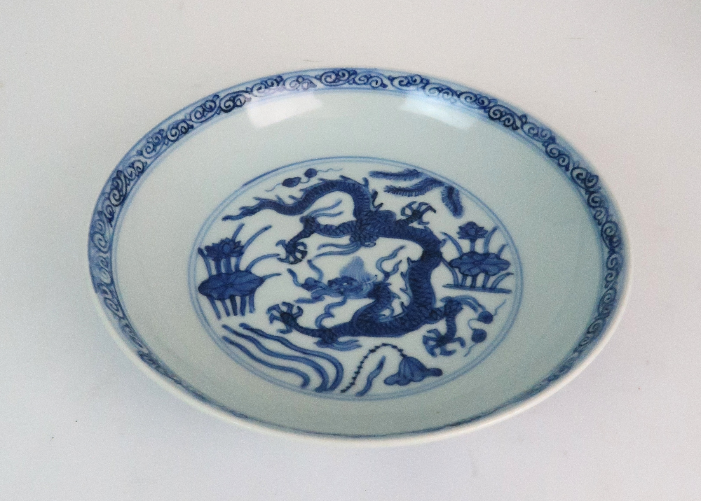 A CHINESE BLUE AND WHITE DISH painted with dragons amongst aquatic foliage, within a scrolling