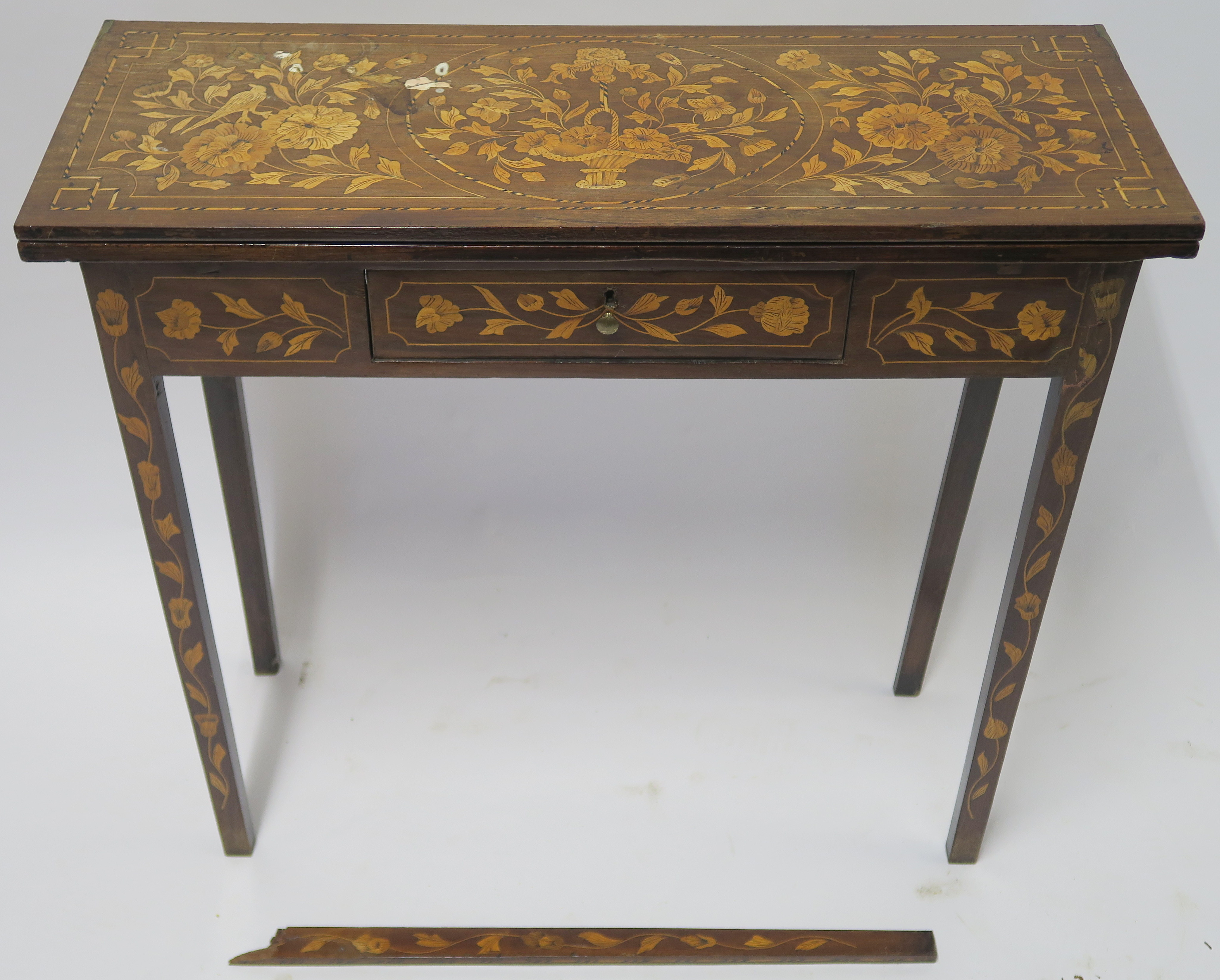 A DUTCH MARQUETRY WALNUT GAMES TABLE decorated with a basket of flowers, birds and scrolling