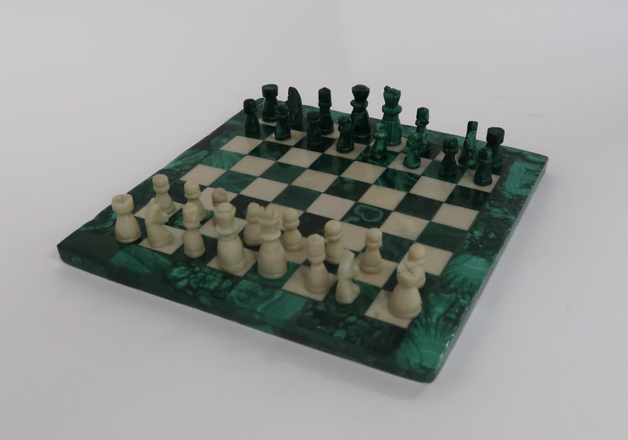 A MINIATURE MALACHITE CHESS SET AND BOARD 19cm square Condition Report: Available upon request
