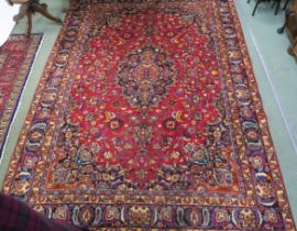 A red ground Mashad rug with blue central medallion, spandrels and borders, 330cm x 240cm