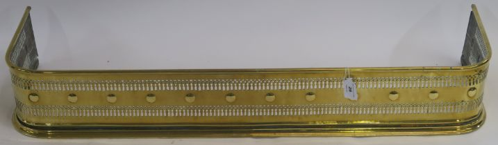 A pierced brass fender, 16cm high x 102cm wide x 32cm deep Condition Report: Available upon request