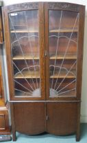 An Art Deco oak bookcase with sunburst leaded glass with carved top over two doors,183cm high x 92cm