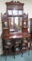 A Victorian mahogany display cabinet with pierced fret work on glazed doors and open shelves with an