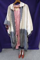 A cream ground embroidered Bedouin cloak with pink rope tassel fastenings and a pair of 1920s ruby