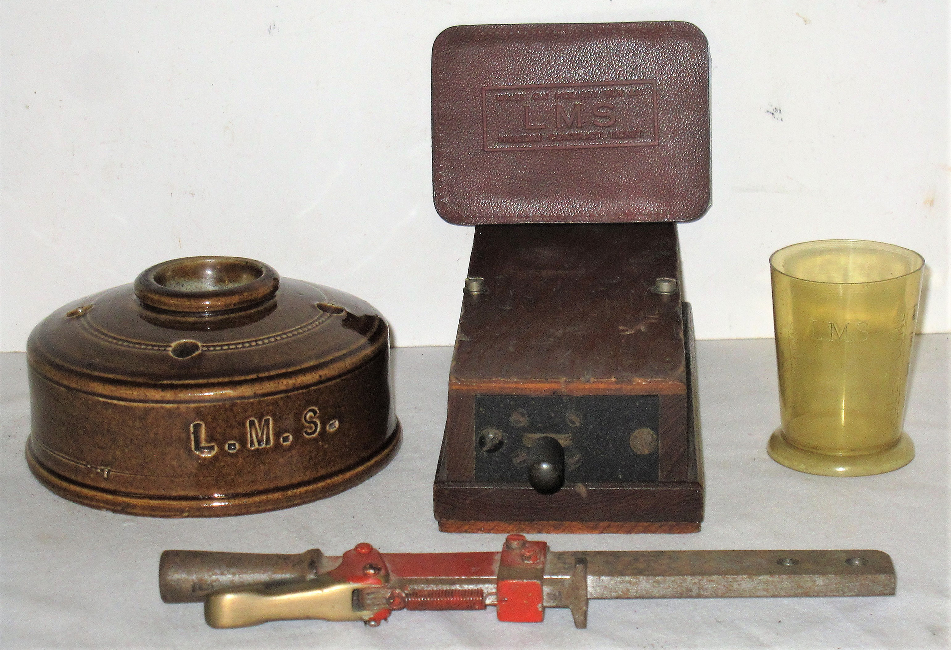 A Lot containing various railway items to include an LMS land mine ink well. LMS leather address