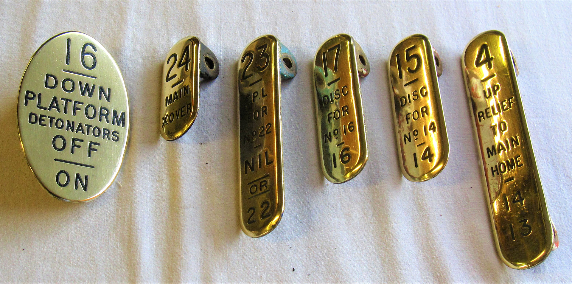A lot containing a collection of GWR brass lever leads to include oval 16 DOWN DETONATORS. 24 MAIN X