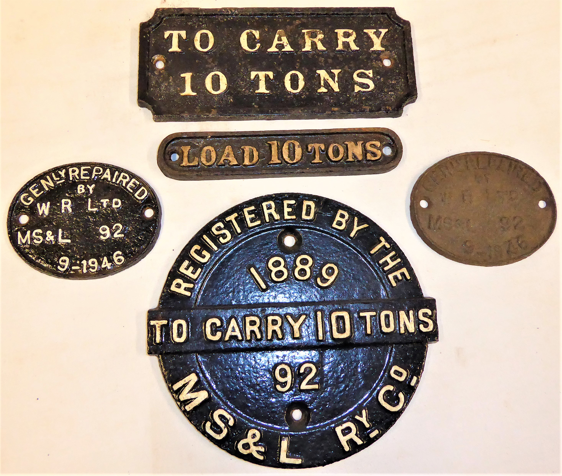 A collection of cast iron Wagon Plates which appear to be recovered from the same vehicle. TO