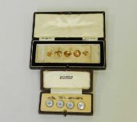 A cased collection of graduated yellow metal studs