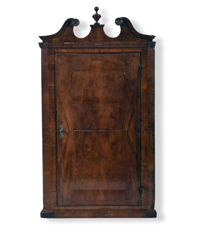 A George II walnut veneered hanging corner cupboard