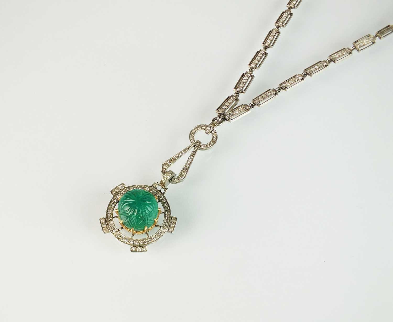 An Art Deco emerald and diamond pendant on chain
