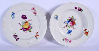 TWO 18TH CENTURY CONTINENTAL PORCELAIN PLATES painted with flowers under a wrythen moulded border. 2