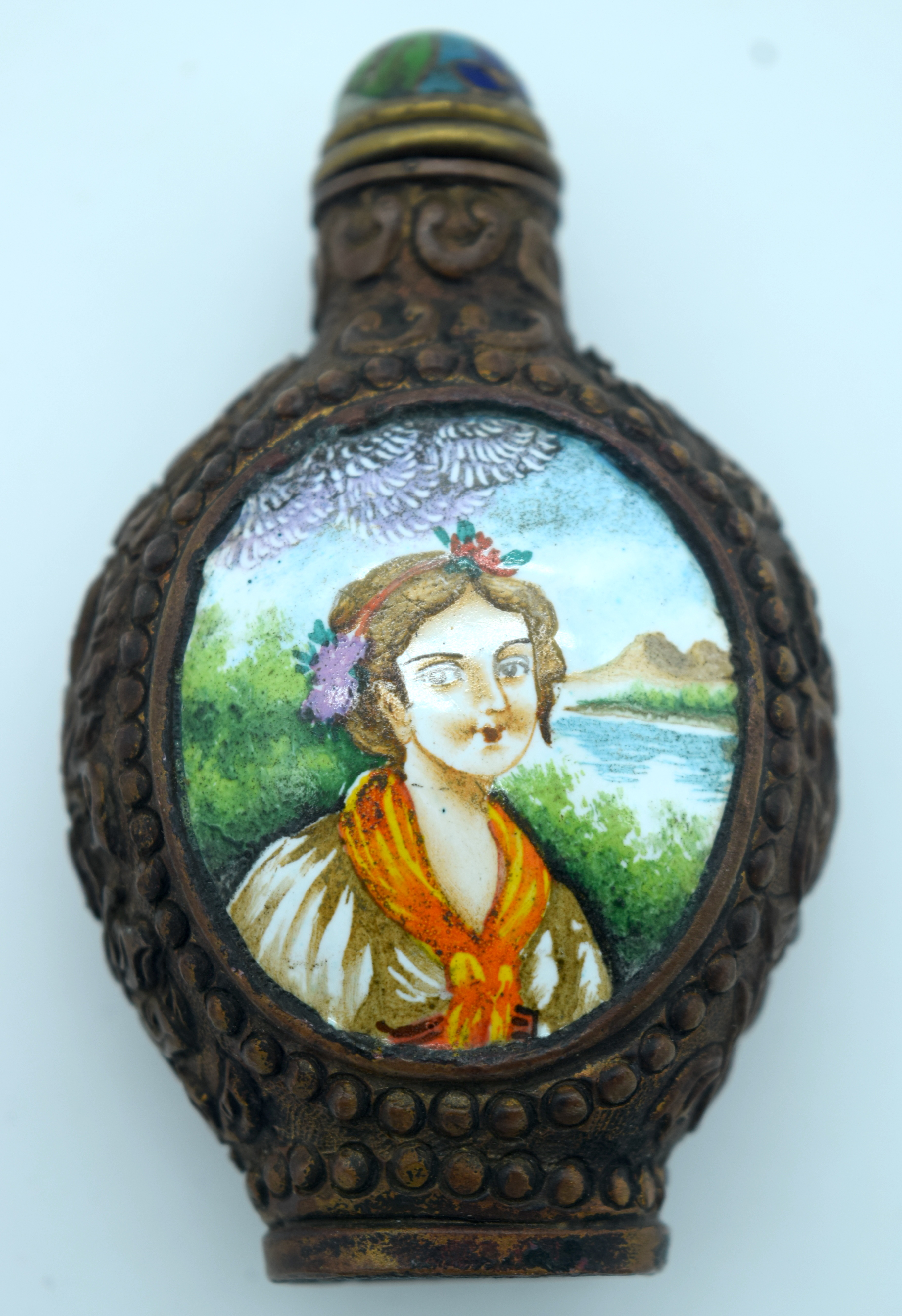A metal snuff bottle with an enamelled painted picture of a woman 8 x 5cm.
