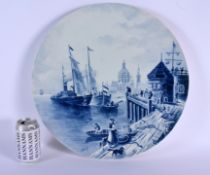 A VERY LARGE CONTINENTAL BLUE AND WHITE POTTERY CHARGER decorated with boating scenes. 45 cm diamete
