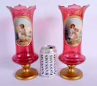 A PAIR OF 19TH CENTURY BOHEMIAN RUBY GLASS VASES painted with girls within landscapes. 27 cm high.
