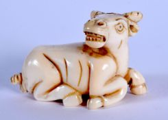 AN EARLY 20TH CENTURY JAPANESE MEIJI PERIOD CARVED IVORY NETSUKE formed as a rearing bullock. 3 cm x