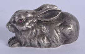 A CONTINENTAL SILVER AND RUBY EYED FIGURE OF A RABBIT. 53 grams. 5.5 cm x 3 cm.