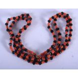 AN ART DECO CORAL AND JET NECKLACE. Each strand 30 cm long.