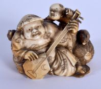A 19TH CENTURY JAPANESE MEIJI PERIOD CARVED IVORY OKIMONO modelled as a male playing an instrument.