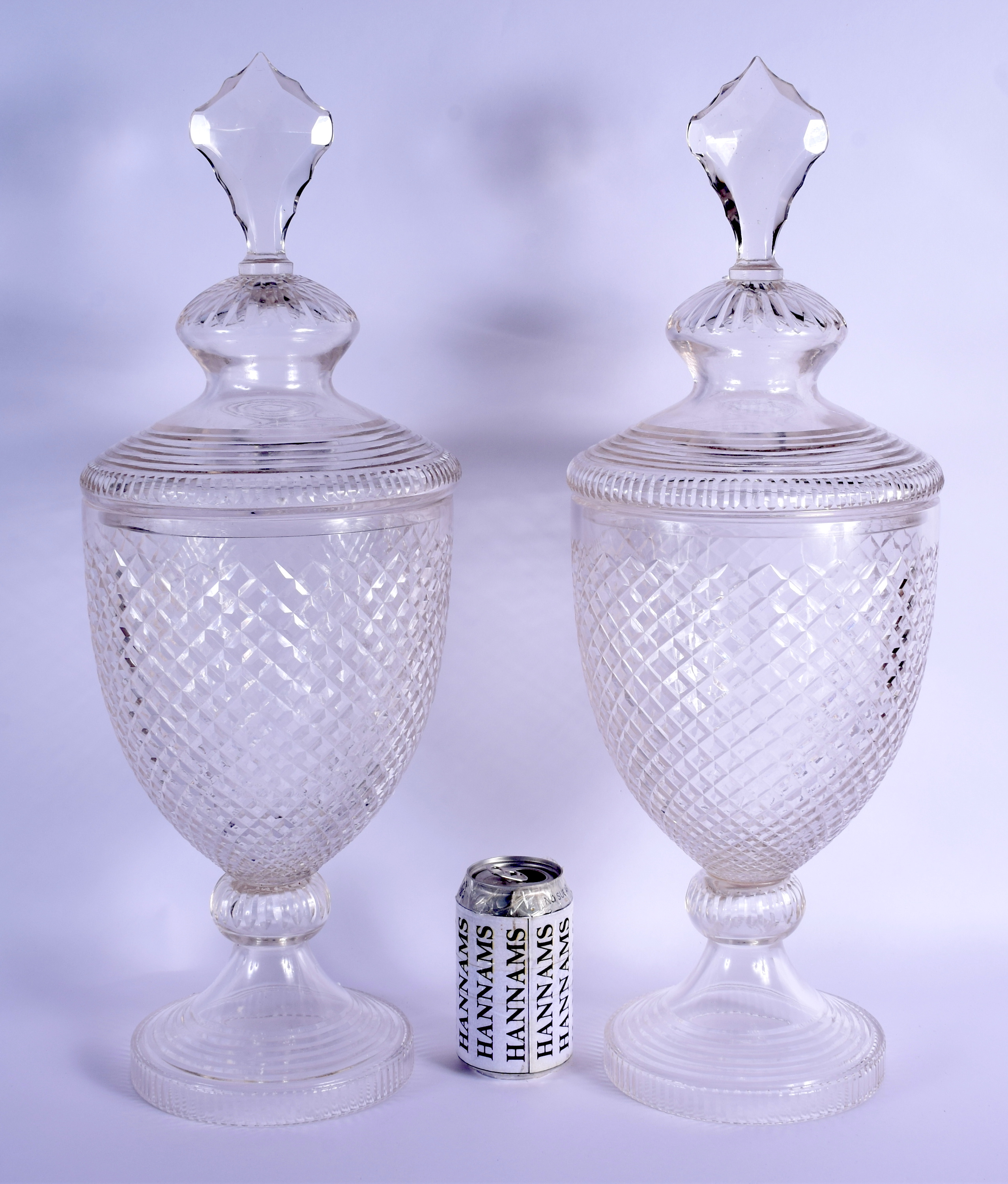 A PAIR OF CUT GLASS STORM LAMPS AND COVERS. 53 cm high.