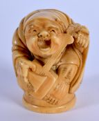 A 19TH CENTURY JAPANESE MEIJI PERIOD CARVED BONE OKIMONO modelled as a musician. 3.5 cm x 2.75 cm.